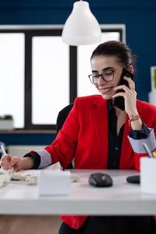 Consulente finanziario che discute con il cliente durante la conversazione telefonica guardando il documento ufficiale