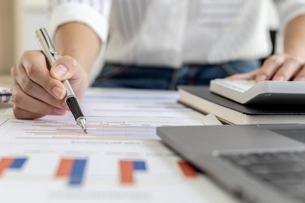 Donna d'affari finanziaria che preme una calcolatrice bianca, usa una calcolatrice per calcolare i numeri nei documenti finanziari dell'azienda che i dipendenti del dipartimento creano come documenti di riunione.