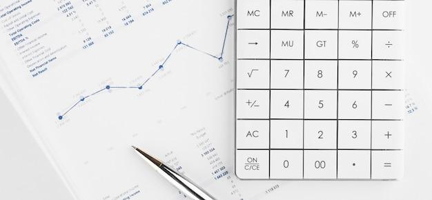 Grafici finanziari e una calcolatrice sulla scrivania del contabile. calcolo dei profitti, tasse e pagamento degli stipendi dei dipendenti.