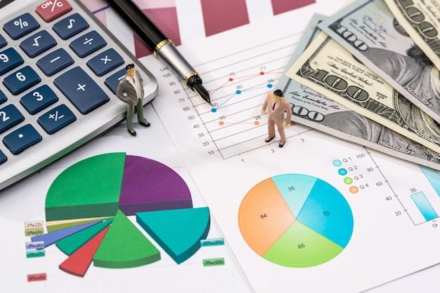 Grafici finanziari con dollari, calcolatrice e piccoli giocattoli