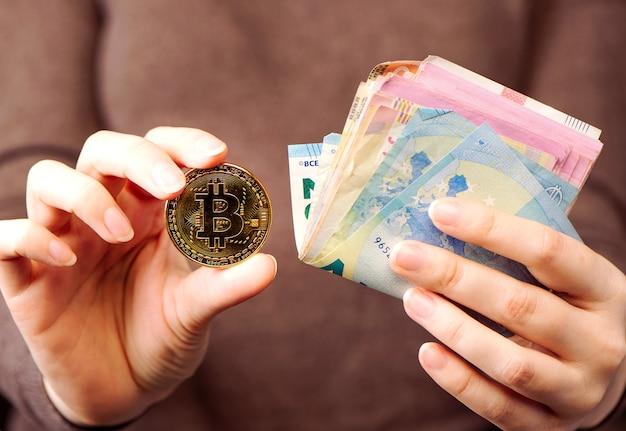 Concetto finanziario, fare soldi online, vendere beni online tramite il concetto di internet. le mani tengono una pila di soldi e bitcoin. avvicinamento.