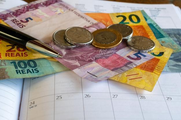 Concetto di controllo finanziario con penna calendario e aumento del salario minimo in denaro brasiliano