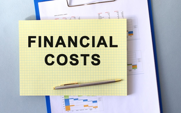 Testo di costi finanziari scritto sul blocco note con la matita. blocco note su una cartella con diagrammi. concetto finanziario.