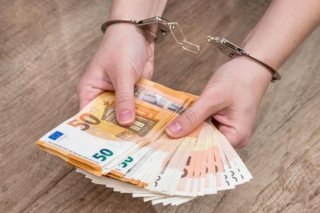 Concetto di criminalità finanziaria - mano femminile con manette e banconote da 50 euro