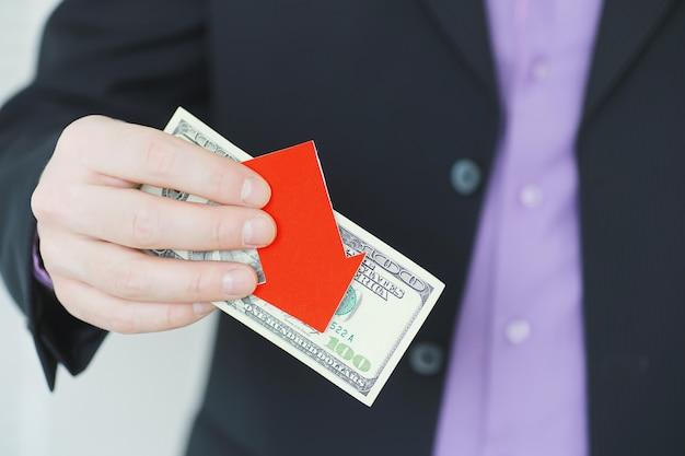 Concetto di crisi finanziaria fatture di denaro in mano simbolo della freccia della caduta della valuta nazionale