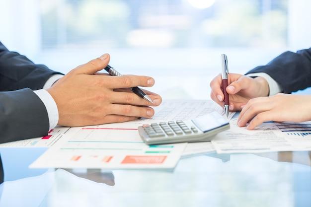 Analisi dei dati finanziari. gente di affari del primo piano con calcolatrici e laptop in ufficio.