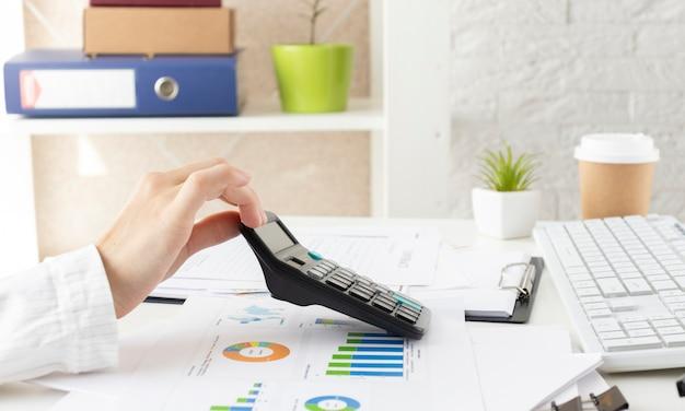 Dati finanziari che analizzano la scrittura a mano e contano sulla calcolatrice in ufficio sulla scrivania in legno