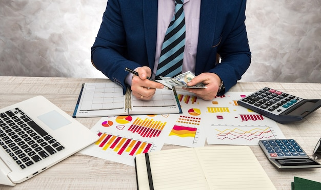 Ispettore finanziario che fa rapporto rapporto di pianificazione finanziaria utilizzando carta per grafici e laptop per reddito o budget di vendita in quest'anno.