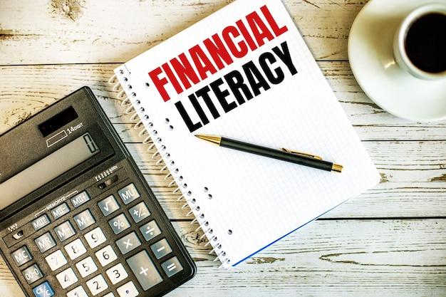 Letterazione finanziaria scritta su carta bianca vicino a caffè e calcolatrice su un tavolo in legno chiaro