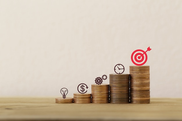 Gestione finanziaria / obiettivi concetto di investimento patrimoniale: disporre l'icona del piano aziendale su file di monete in aumento, dimostrando prestazioni eccellenti attraverso l'organizzazione di un portafoglio per il massimo profitto.