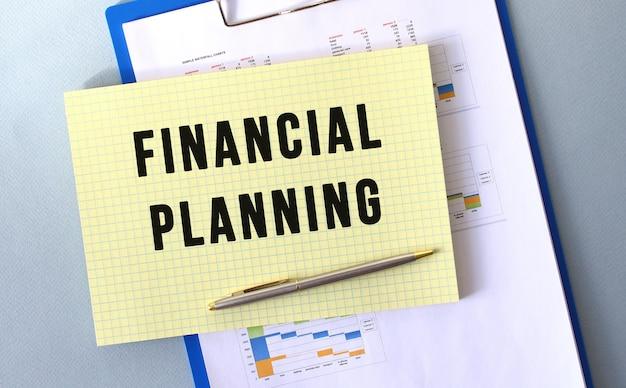 Testo di pianificazione finanziaria scritto sul blocco note con la matita. blocco note su una cartella con diagrammi. concetto finanziario.