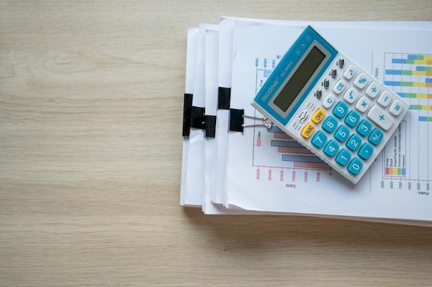 Carta per rapporti finanziari e macchina di calcolo sulla scrivania dell'ufficio, concetti di finanza e contabilità