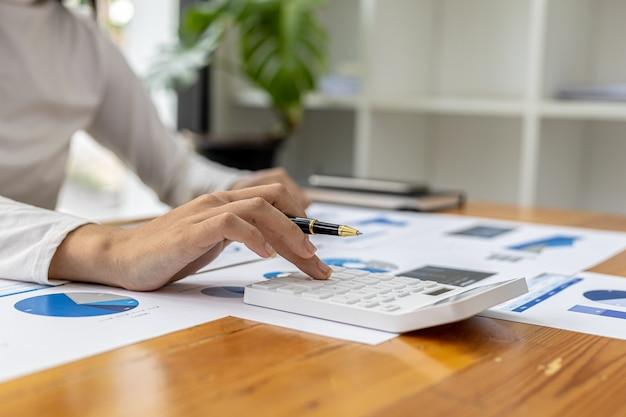 Una studiosa finanziaria sta indicando un documento con una penna, sta analizzando e controllando l'accuratezza dei dati finanziari dell'azienda prima di presentarli alla riunione. concetto di audit finanziario.