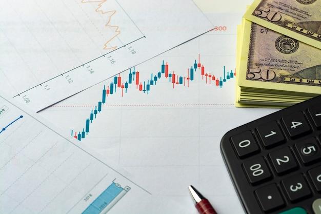 Bilancio d'esercizio. grafico commerciale. penna e calcolatrice con banconote in dollari su un grafico finanziario o dati del mercato azionario.