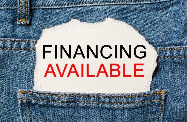 Finanziamento disponibile su sfondo di carta strappata su jeans business e concetto di finanza