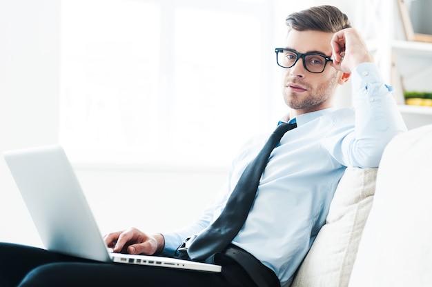 Trovare un posto tranquillo per il lavoro. fiducioso giovane uomo d'affari che lavora al computer portatile