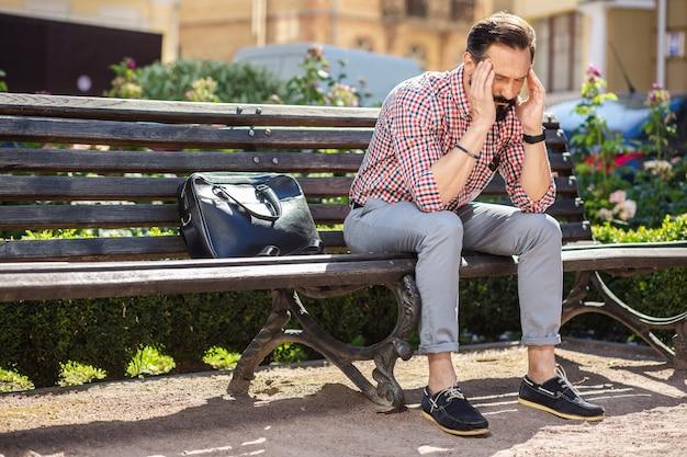 Trovare la via d'uscita. uomo depresso lunatico che si sente stanco mentre è seduto sulla panchina
