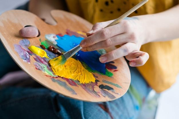 Scuola d'arte. primo piano della tavolozza in legno con vernice acrilica e pennello nelle mani dell'artista.