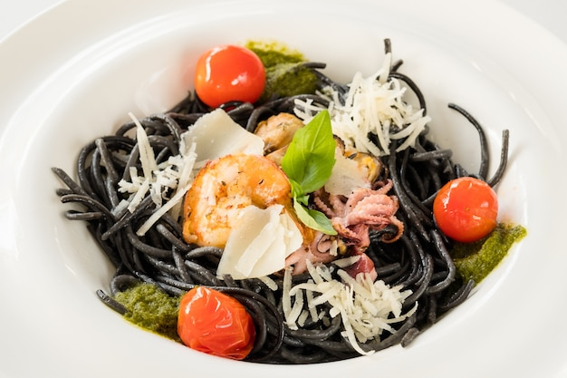 Composizione del cibo di cucina raffinata. pasta nera fresca con pollo e pomodoro.