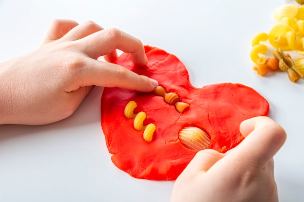 Abilità motorie eccellenti. creatività dei bambini. modellazione di plastilina per lo sviluppo del bambino a casa. mani del bambino che creano cuore dall'impasto per modellare. gioco antistress con la pasta.
