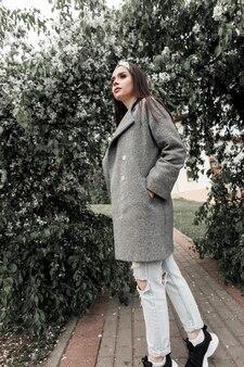 Bel ritratto giovane donna in bandana vintage in cappotto grigio alla moda vicino a fogliame verde nel parco. modello di ragazza carina in abiti alla moda cammina e gode della bellezza della natura. bella signora alla moda.