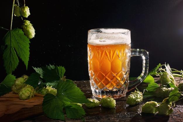 Bella birra gialla non filtrata in boccale trasparente su sfondo nero con germogli di luppolo.
