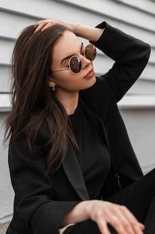Il modello di moda della giovane donna fine in occhiali da sole alla moda in vestiti neri alla moda raddrizza l'acconciatura vicino alla parete di legno in città. ragazza moderna abbastanza sexy in abbigliamento casual sedersi su piastrelle di pietra in strada.