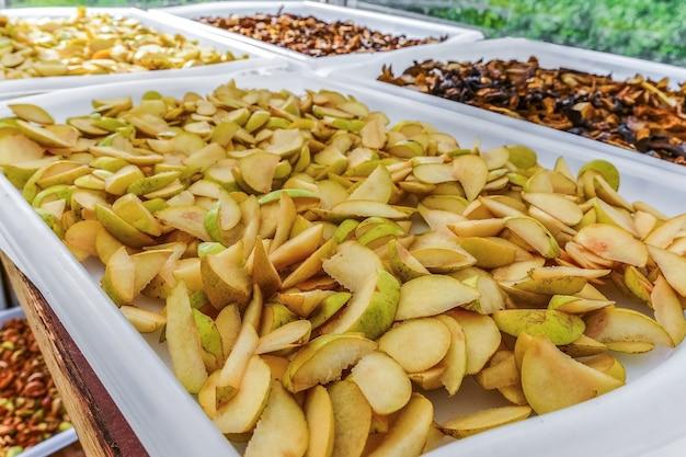 Pere tritate finemente, mele e altri frutti vengono essiccati in un essiccatore naturale all'aperto in una giornata di sole