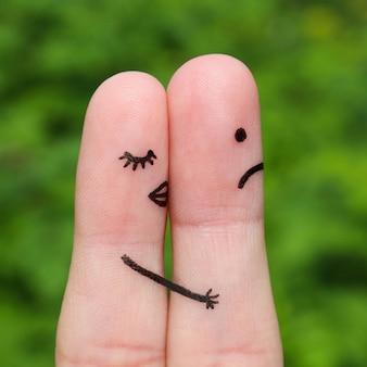 Arte delle dita di coppia. una donna bacia un uomo, non le piace. il concetto non è amore condiviso.