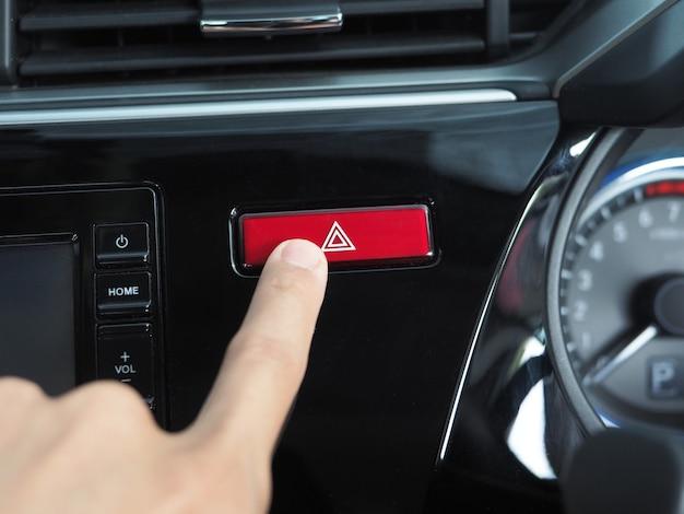Dito sul pulsante di emergenza dell'auto lucida e pulita
