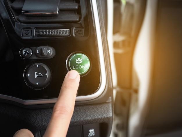Dito sul pulsante della modalità di risparmio energetico dell'auto ecologica con bagliore di luce