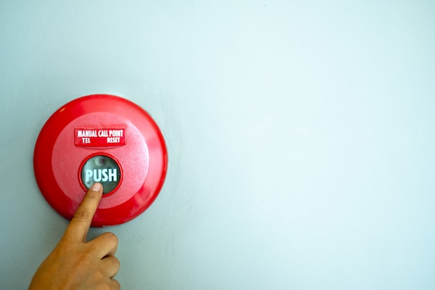 Il dito sta spingendo un'attrezzatura del bottone dell'allarme antincendio sui precedenti della parete