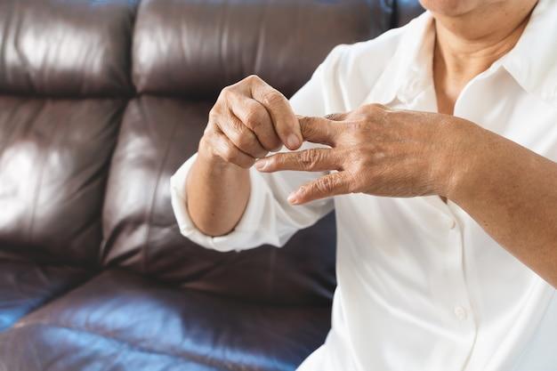 Dolore al dito della donna anziana, problema sanitario del concetto senior