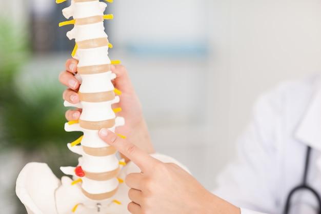 Dito che punta all'osso nella spina dorsale
