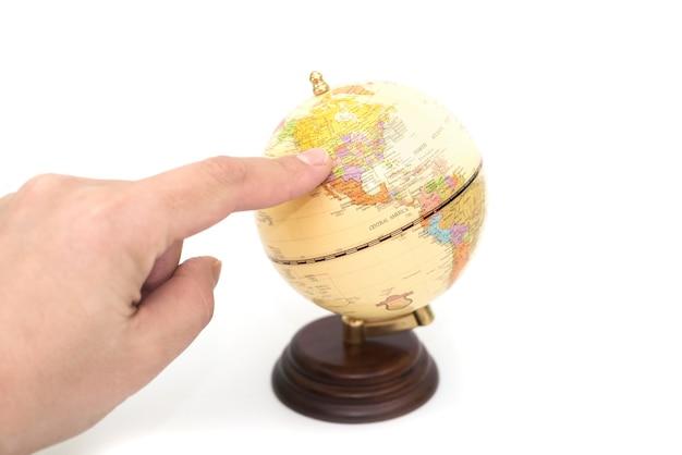 Il dito indica gli stati uniti sul globo. isolato.