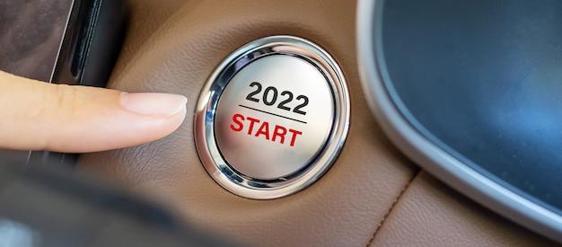 Premere con le dita un pulsante di accensione dell'auto con il testo start 2022 all'interno di una moderna automobile elettrica. anno nuovo nuovo te, risoluzione, cambiamento, obiettivo, visione, innovazione e concetto di pianificazione
