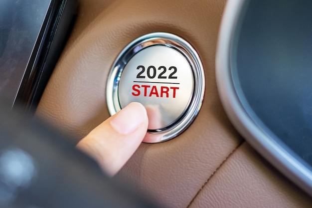 Premere con le dita un pulsante di accensione dell'auto con il testo start 2022 all'interno di una moderna automobile elettrica. anno nuovo nuovo tu, risoluzione, cambiamento, obiettivo, visione, innovazione e concetto di pianificazione