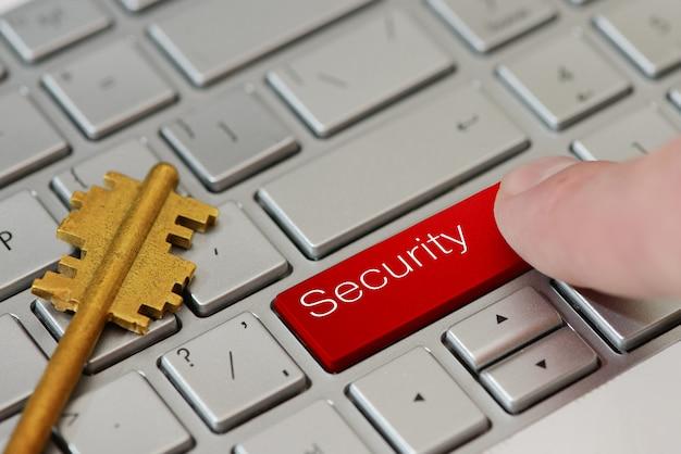 Un dito preme un pulsante rosso con testo sicurezza sulla tastiera del laptop.