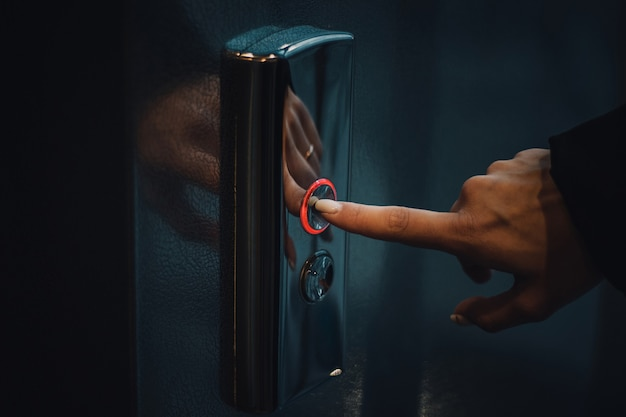 Dito che preme il pulsante dell'ascensore