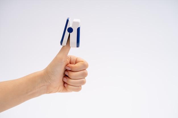 Pulsossimetro da dito. su sfondo bianco. il dispositivo è posizionato con il pollice in su. diagnostica sanitaria.