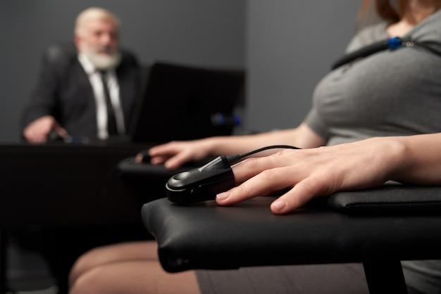 Sensore di dito e filo del rivelatore di bugia sulla mano femminile.