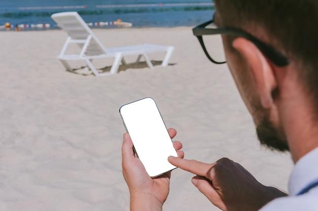 Tocco delle dita, simulare lo smartphone nella mano di un uomo sulla spiaggia con una sedia a sdraio. sullo sfondo di sabbia e acqua.