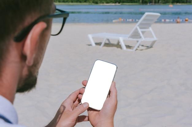 Tocco delle dita, simulare lo smartphone nelle mani di un uomo sulla spiaggia con una sedia a sdraio. sullo sfondo di sabbia e acqua.