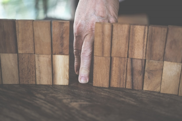 Dito a piedi attraverso il muro fatto da blocchi di legno.