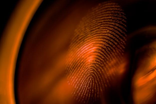 Macro di impronte digitali su una lente in luce rossa, profondità di campo. concetto biometrico e di sicurezza.