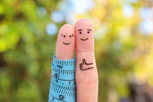Arte delle dita di una coppia felice con la misura di nastro. concetto di perdere peso insieme.