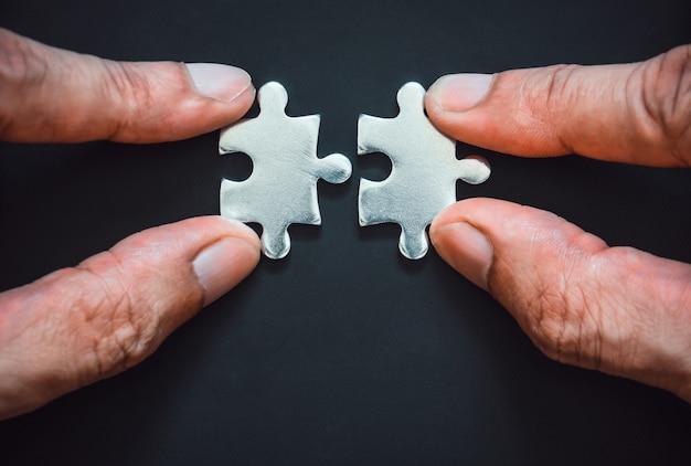 Le dita collegano i pezzi del puzzle in metallo argentato su sfondo nero