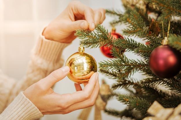 Ritocchi finali. sguardo ingrandito sulle mani femminili che tengono una palla dorata lucida mentre si trova su un albero e lo decora per natale.