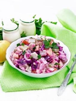Insalata finlandese rosoli di aringa, barbabietola, patate, sottaceti, carote, cipolle e uova, conditi con maionese in una ciotola su fondo di legno