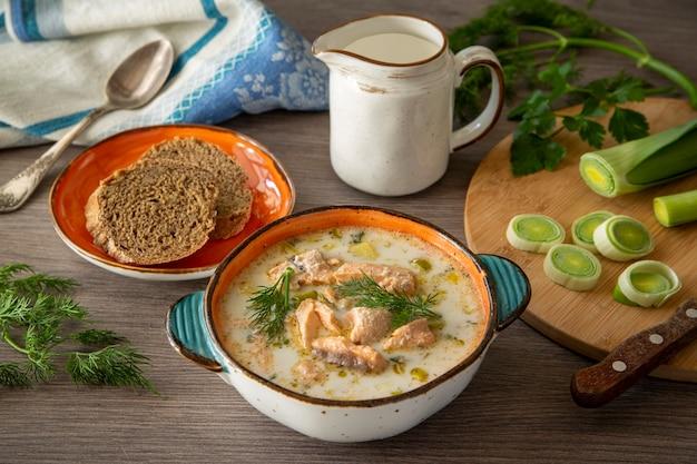 Zuppa di salmone finlandese con porri e panna su uno sfondo di tavolo in legno cibo sano cibo tradizionale